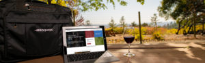 glass of wine and laptop outside on picnic table